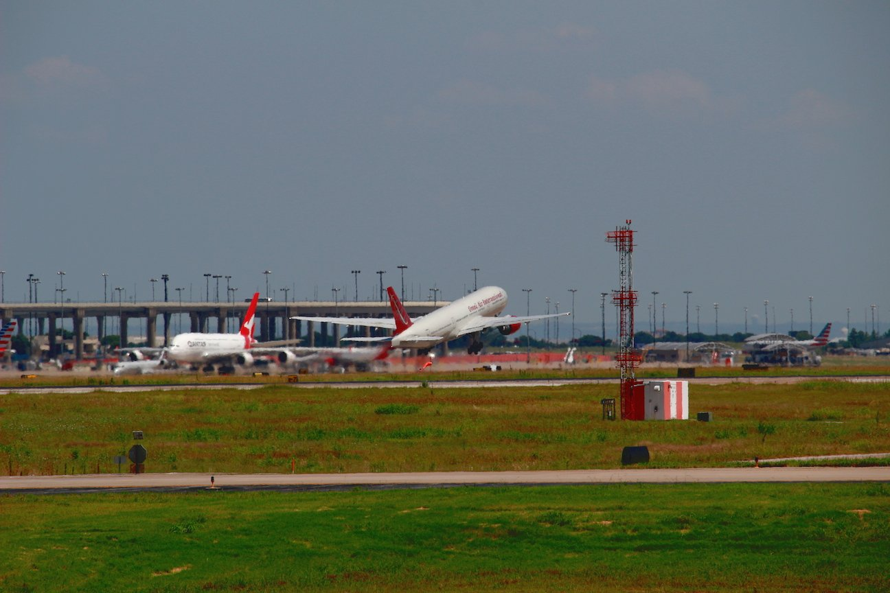 Omni Air International 767 taking off into the south. A Qantas A380 is parked on the tarmac in the background.